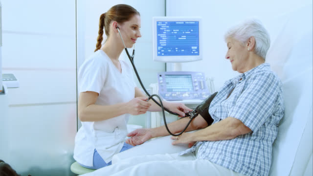 Nurse measuring a womans blood pressure video