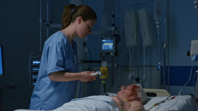 ds infermiera di temperatura di pazienti in terapia intensiva - carrellata video stock e b–roll