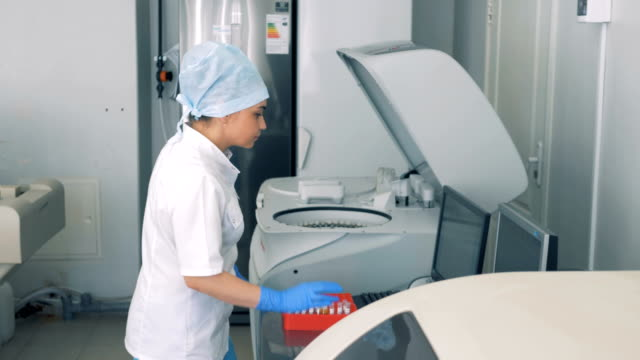 A nurse performs blood tests, using modern automated medical equipment.