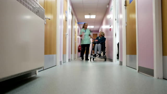 Nurse Pushes Elderly Woman Down Corridor In Wheelchair A nurse can be seen pushing an elderly lady in a wheelchair down a corridor. It's shot in a typically British hospital. nhs stock videos & royalty-free footage