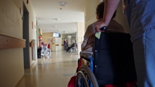 WS Nurse pushing elderly woman on wheelchair Wide shot of a caring nurse pushing senior woman on wheelchair down the hall at the nursing home. pushing wheelchair stock videos & royalty-free footage