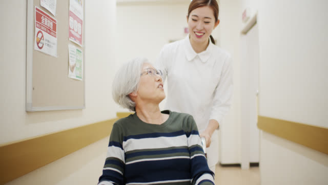 Nurse Pushing Patient in Wheelchair Down Hospital Corridor Patients and healthcare professionals at a hospital or medical clinic in Tokyo, Japan. pushing wheelchair stock videos & royalty-free footage