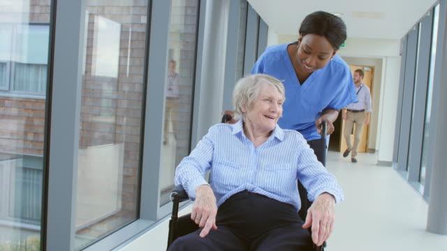 sjuk sköterska pushing senior patient i rullstol längs korridoren - omsorg bildbanksvideor och videomaterial från bakom kulisserna
