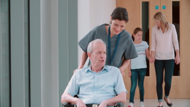 vídeos de stock e filmes b-roll de enfermeira empurrando paciente idoso em cadeira de rodas ao longo corredor - empurrar atividade física