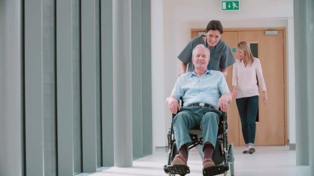 Nurse Pushing Senior Patient In Wheelchair Along Corridor Nurse Pushing Senior Patient In Wheelchair Along Corridor pushing wheelchair stock videos & royalty-free footage