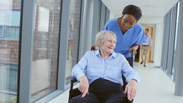 Nurse Pushing Senior Patient In Wheelchair Along Corridor video