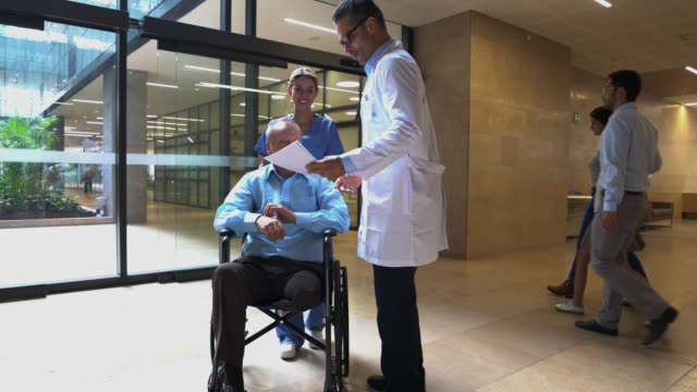 Nurse pushing wheelchair with senior amputee patient while he greets doctor both looking at some test results very happy Nurse pushing wheelchair with senior amputee patient while he greets doctor both looking at some test results very happy - Incidental people at background entrance stock videos & royalty-free footage