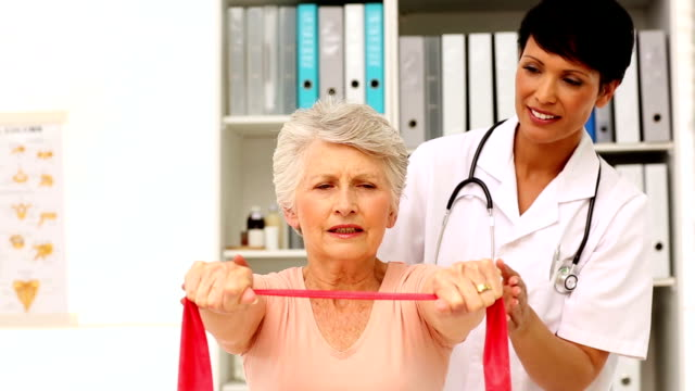 Nurse showing elderly patient how to use resistance band video