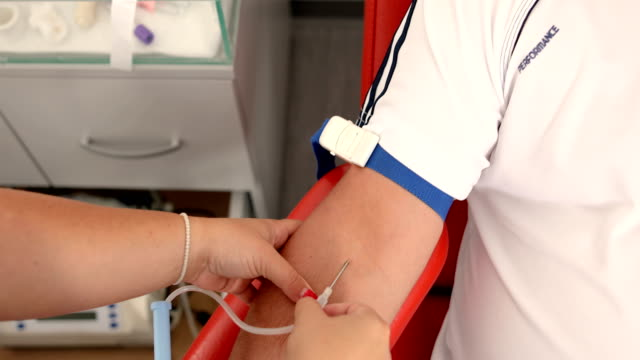 nurse stabbing medical needles to donor arm.good deed.benefits of donating blood for your body.the hand of recipient receiving the blood transfusion.close up of blood donor giving blood in medical clinic - cucitura video stock e b–roll