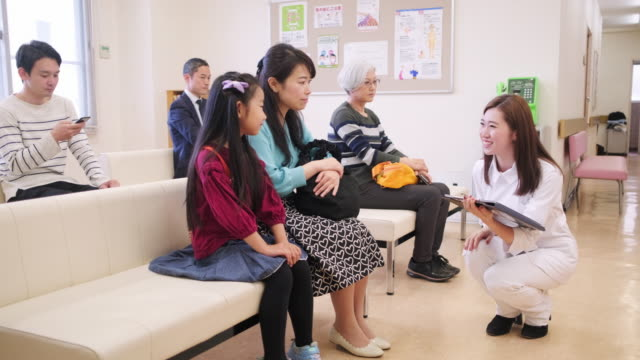 nurse taking little girl and her mother into the doctor's office - età miste video stock e b–roll