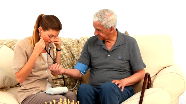 Nurse taking the blood pressure of her male patient video