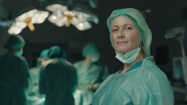 hemşire ameliyat maskesi alıyor - cerrahi önlük stok videoları ve detay görüntü çekimi