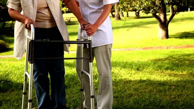 Nurse talking to woman using walker outside video