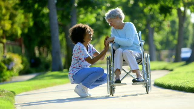 Nurse talking with elderly woman in wheelchair video