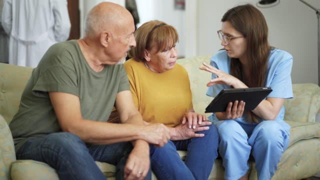 vídeos y material grabado en eventos de stock de enfermera hablando con la pareja de la tercera edad en el hogar de ancianos - geriatría