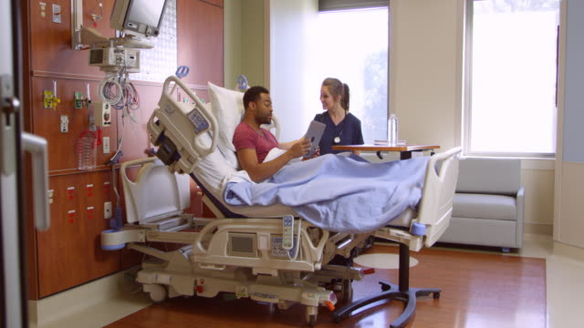 Nurse Talks To Male Patient In Hospital Bed Shot On R3D video