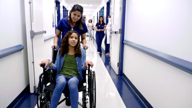 nurse talks with female preteen patient as she pushes the girl in the wheelchair - inserviente medico video stock e b–roll