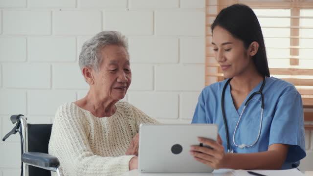 高齢の女性と話をするためにタブレットを使用して看護師.健康訪問者と家庭訪問中にタブレットを持つ先輩女性。 - 老人ホーム点の映像素材/bロール