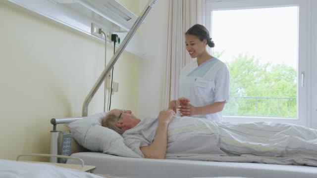 病室で高齢者を訪問する看護師 ビデオ