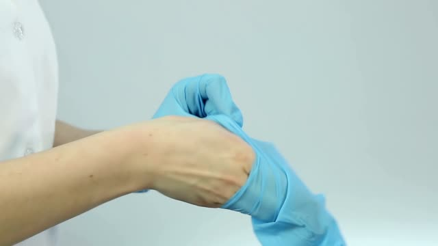Nurse wearing medical gloves before treatment procedures, patient examination video