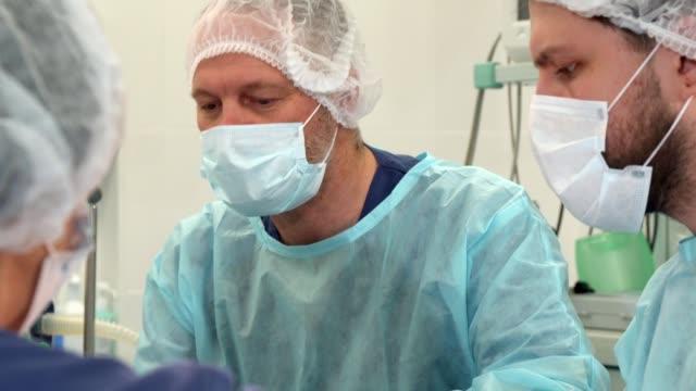 vidéos et rushes de infirmière essuie le front du chirurgien à la chirurgie - réfracteur
