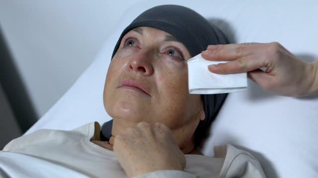 vídeos y material grabado en eventos de stock de enfermera limpiando lágrimas de anciana con cáncer, rehabilitación después de la quimioterapia - geriatría
