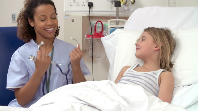 Nurse With Stethoscope Examining Young Girl In Hospital Bed video