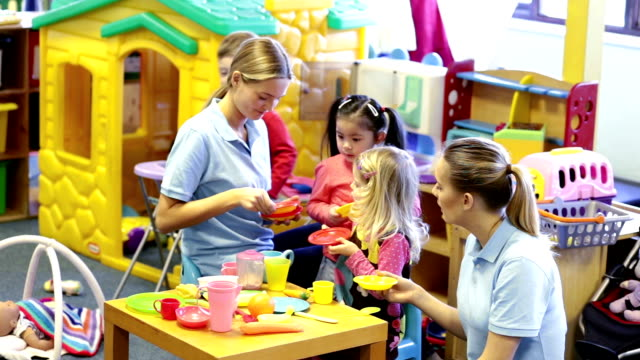 Nursery Playtime Young children gather around a table in their nursery to play. Young nursery teachers interact with the children. child care stock videos & royalty-free footage