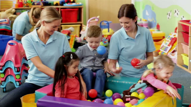 Nursery Playtime A group of young children and nursery school workers are gathered around a ball pool playing. While the teachers supervise child care stock videos & royalty-free footage
