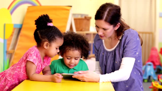 Nursery worker teaching children how to use a digital tablet Preschool children sitting looking at a digital tablet whilst nursery teacher demonstrates how to use it. child care stock videos & royalty-free footage