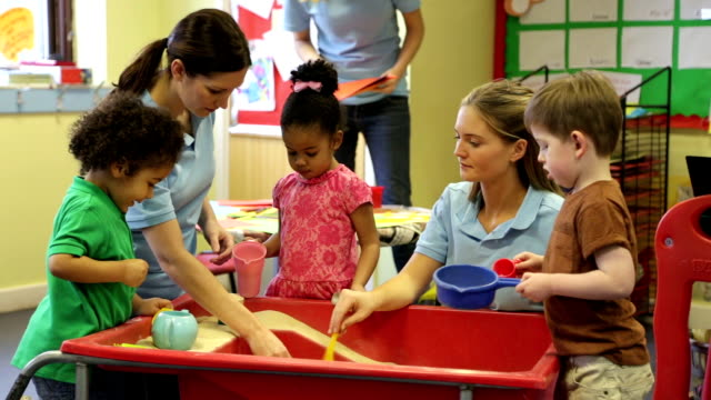 Nursery workers with children playing in the sandpit Preschool children standing playing with the teachers around an indoor sandpit. child care stock videos & royalty-free footage