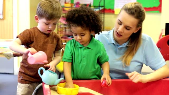 vídeos de stock, filmes e b-roll de berçário trabalhadores com crianças brincando no areeiro - professor de pré escola