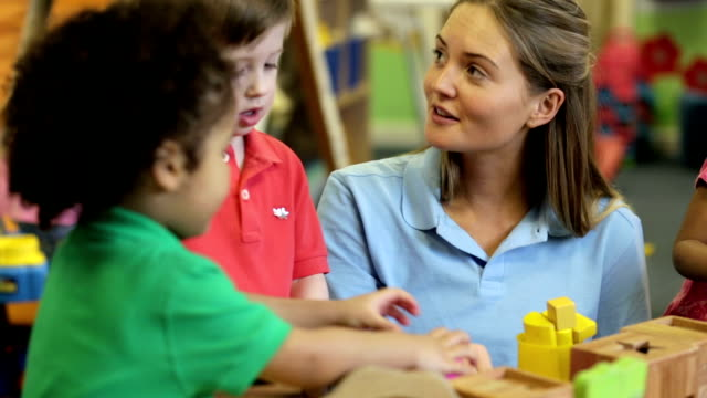 Nursery workers with children playing with toys video