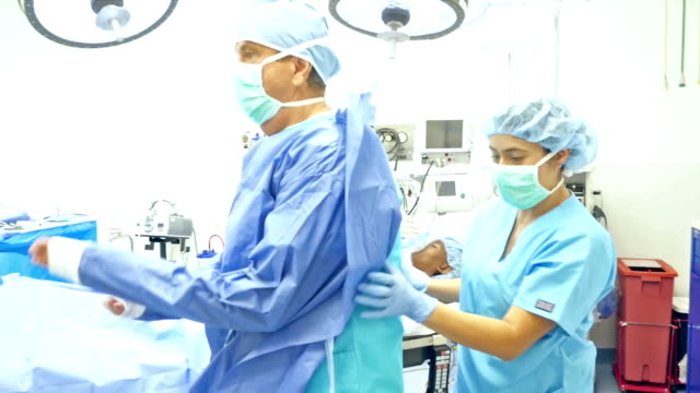 Nurses assist surgeon with protective clothing