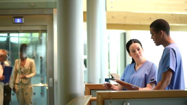 vidéos et rushes de infirmières vérification des notes dans un couloir de l'hôpital - infirmier