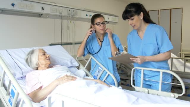 nurses communicating while examining senior woman - nurse stock videos & royalty-free footage