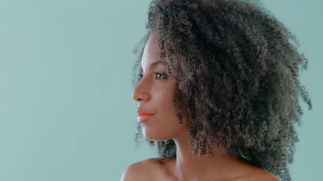 Nurturing this black crown of hers 4k video footage if an attractive young woman combing her hair while standing against a green background curly hair stock videos & royalty-free footage