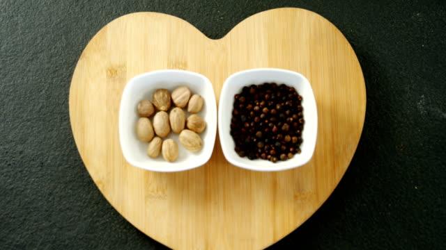 Nutmeg and black pepper on heart shape board 4k video