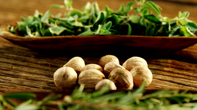 Nutmeg and herbs on a wooden table 4k video