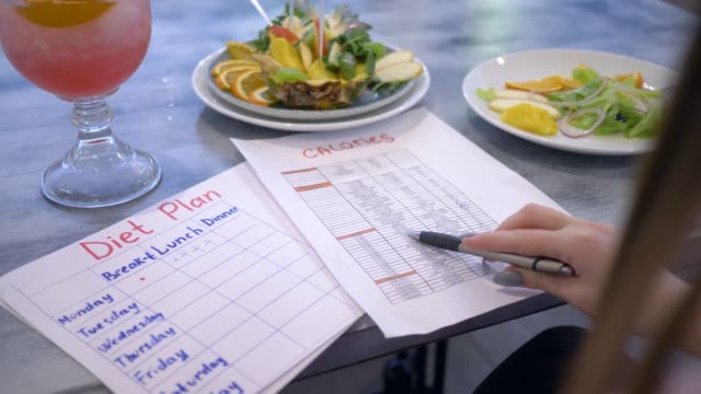 nutritionist female looking for calories in list and hold in hand diet plan sitting at the table with punch and fruits in plate