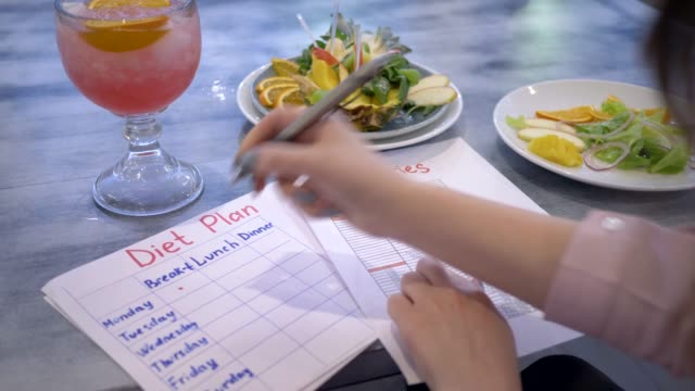 nutritionist woman writes diet plan with food calorie sheet on table with punch and fruits in plate at cafe nutritionist woman writes diet plan with food calorie sheet on table with punch in glass and fruits in plate at cafe nutritionist stock videos & royalty-free footage