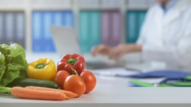 Nutritionist working in the office Professional nutritionist working in the office, she is connecting and typing on a laptop, fresh healthy vegetables on the foreground nutritionist stock videos & royalty-free footage