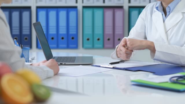 Nutritionist working in the office Professional dietician working in the office, she is shaking hands with a patient and explaining a prescription diet, healthy fruit and tape measure on the foreground nutritionist stock videos & royalty-free footage