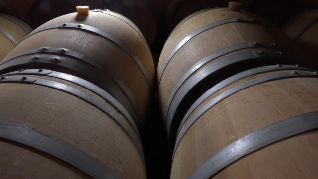 oak barrels of wine in the cellar, bordeaux vineyard, france - vite flora video stock e b–roll