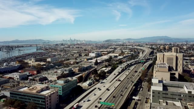 Oakland 880 Freeway with San Francisco View Aerial view of the 880 Freeway in Oakland with a clear view of the Bay Bridge and skyline of San Francisco on a sunny day. Moderate traffic on the freeway. Port of Oakland and Alameda shipping bay is visible across the freeway. oakland stock videos & royalty-free footage