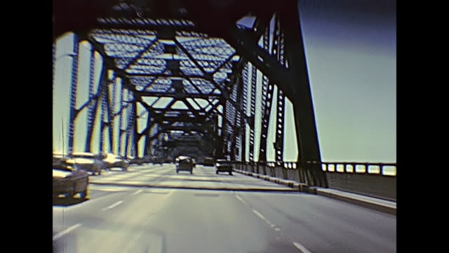 Oakland Bay Bridge POV of vintage car crossing Oakland Bay Bridge passing by Treasure Island to Oakland. Archival footage in eighties. San Francisco, California, United States in 1980. the past stock videos & royalty-free footage