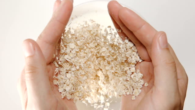 vídeos de stock e filmes b-roll de slow motion: oat flakes falls from a human hands to the milk in a dish - oats