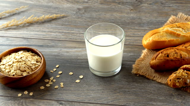 Oatmeal in a bowl, glass of milk and fresh homemade baguettes on a rustic wooden table video