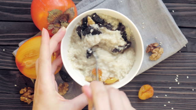 Oatmeal porridge. Healthy food Young woman stirs porridge top view. Stirring oatmeal in a deep bowl. Healthy breakfast- oatmeal with persimmon, dried apricots, prunes, walnuts and sesame. table top view stock videos & royalty-free footage