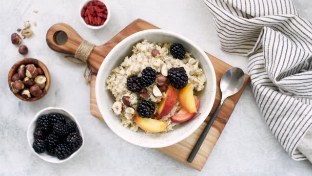 vídeos de stock e filmes b-roll de oatmeal porridge with berries fruits and nuts - granola
